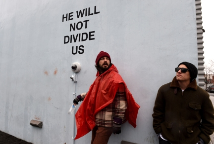 US actor Shia LaBeouf(L)is seen during his He Will Not Divide Us livestream outside the Museum of the Moving Image in Astoria, in the Queens borough of New York January 24, 2017 as a protest against President Donald Trump. LaBeouf has installed a camera at the Museum of the Moving Image in New York that will run a continuous live stream for the duration of Trumps presidency. LaBeouf is inviting the public to participate in the project by saying the phrase, He will not divide us, into the camera. / AFP / TIMOTHY A. CLARY (Photo credit should read TIMOTHY A. CLARY/AFP/Getty Images)